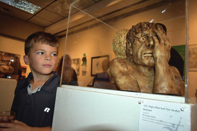 Cody Willoughby | Troy Daily News Trevar Martin, 9, of Greenville examines a sculpture on display in the Art of Recovery gallery during the Tri-County Board of Recovery and Mental Health Services 50th anniversary celebration on Wednesday at Edison State Community College.