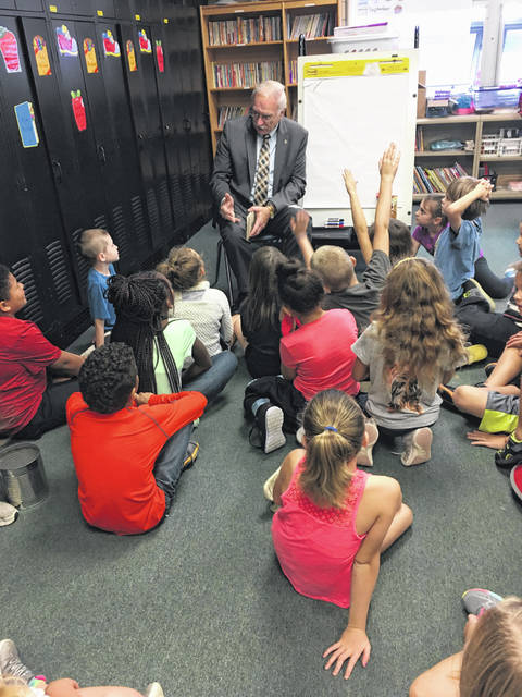 "Sidney Mayor Mike Barhorst reads from one his favorite books, ""Mr. Michael Mouse Unfolds His Tale,"" as part of the Right to Read activities at Emerson Elementary School."
