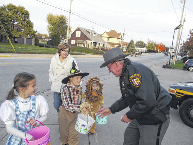 Shelby County Sheriff's Office Reserve Deputy Brooks Mason hands out treats to Dorothy, Scarecrow and the Cowardly Lion during Tuesday night's trick or treat in Botkins. Mason said Botkins was the fourth trick or treat night he's attended this holiday season. He also handed out treats in McCartyville, Anna and Jackson Center.