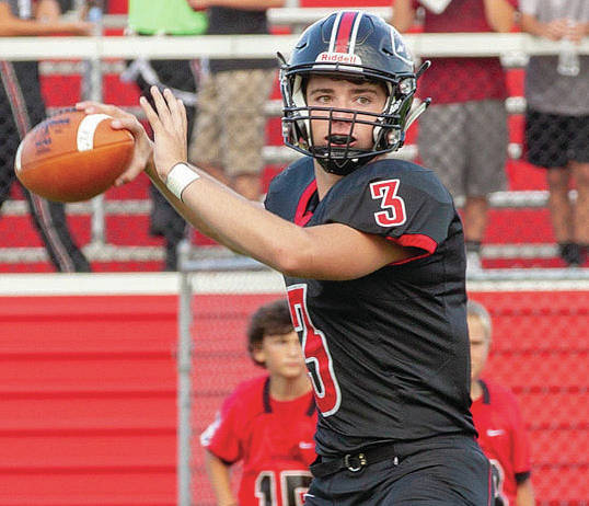 Fort Loramie's Collin Moore prepares to throw during a nonconference game against Minster on Aug. 24 in Fort Loramie. Despite the rain the last two Fridays, Moore has thrown for at least 100 yards each night without an interception.