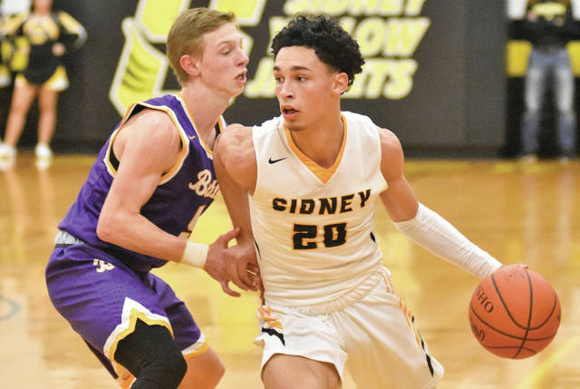 Sidney junior guard Andre Gordon dribbles with pressure from Butler's Kort Justice during a Greater Western Ohio Conference game on Dec. 19, 2017 in Sidney. Gordon verbally committed to Virginia Tech on Monday.