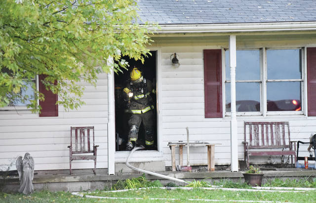 A firefighter surveys the porch of a house that caught fire around 5 p.m. Sunday Oct. 28 at 11033 Township Road 76 in Logan County. Responding to the fire were Quincy, Maplewood and Miami TWP fire departments. No other information was available.