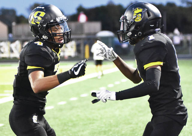 Sidney's Darren Taborn, left, and Quamir Brown celebrate after Taborn scored a touchdown in the second quarter of a Greater Western Ohio Conference American North Division game against Piqua last Friday at Sidney Memorial Stadium.