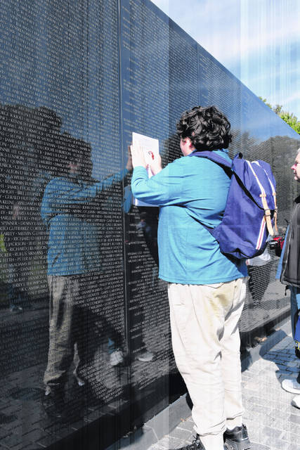 Robbie Lynch uses a pencil and paper to get an etching of a persons name off of the Vietnam Memorial Wall Friday in Washington DC.