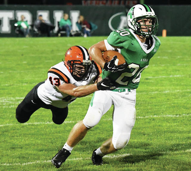 Anna junior running back Riley Huelskamp shakes off Versailles' Tyler Henry during a Midwest Athletic Conference game last Friday in Anna. Huelskamp has rushed for 700 yards and 14 touchdowns this season.