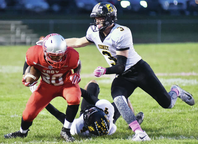 Sidney's Darren Taborn, bottom, and Josh Harlett, right, work bring down Troy's Jacob Shoop during a Greater Western Ohio Conference American North Division game on Friday at Troy Memorial Stadium. Sidney held Troy to 253 yards of offense.
