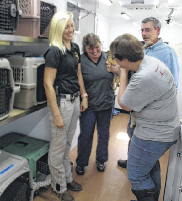 Shelby County Sheriff's Deputy/Dog Warden Kelly Ward, left to right, NOMAD Spay/Neuter Clinic for Cats' mobile veterinarian Dr. Laura Miller and 4th Ward Sidney City Council member Steve Wagner, look at one of the Trap-Neuter-Return program's captured cats held by volunteer and SCARF board member Nicole Laber during a recent clinic.