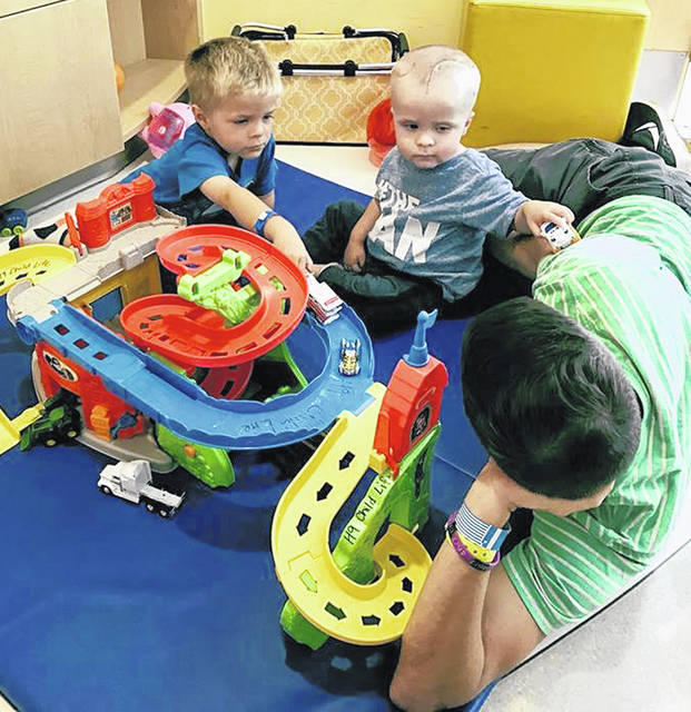 Henry Springer, center, plays with his brother, Eli, and father, Matt, on the floor of an inpatient room at Nationwide Children's Hospital in Columbus. Henry had brain surgery in June to remove a large tumor. He was at Nationwide for a week to receive intense inpatient rehabilitation therapy.