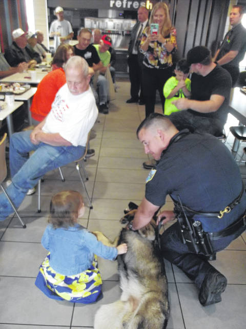 Maisie Dunn, 3, daugher of Heather and Kevin Dunn, of Sidney, was one of the first people to pet Sidney's latest police officer, K-9 Kash, during coffee with a cop Wednesday morning at McDonald's. Talking with Maisie is Kash's handler, Officer Nick Zimmer.
