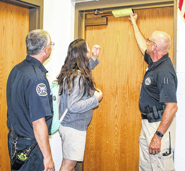 Sidney Fire Lt. Tony McLain, left, Lehman Catholic High School student Carly Caulfield, 17, daughter of Matt and Lynette of Piqua, and Sidney Police Resources Officer Mike McRill, right, are pictured in Lehman's music room on Monday afternoon. McRill is demonstrating how to use a left over piece of a cut fire hose, from the Sidney Fire Department, as a tool to lock a door in the event of an active shooter situation.