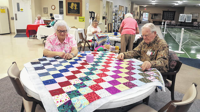 Lynne, left, and Jerry Swaim, of Sidney, knot quilts during a community quilting project at Ohio Living Dorothy Love, recently. Fifty-five volunteers donated a total of 234 hours to make 29 quilts that will be delivered by Quilts of Compassion, of Toledo, to victims of hurricanes in North and South Carolina.