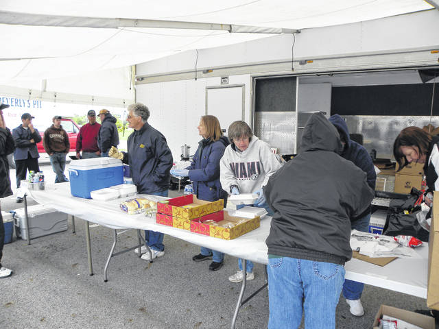 Volunteers ready chicken and pork dinners to sell during a previous sale by the Council of Religious Education. This year's sale will be Saturday, Oct. 20.