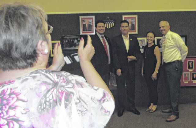 Fran Engle, of Wapakoneta, takes a photograph on her phone of Rob McColley, Craig Riedel, Susan Manchester and Matt Huffman Wednesday night during the opening of the Republican campaign headquarters in Wapakoneta. The headquarters is located in Grandview Plaza on Defiance Street.