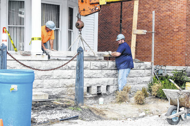 Frederick Keller, left and Bradley Hale, of the Spieker Co., guide a stone as an unseen crane operator swings it into place at the Ross Historical Center in Sidney, Tuesday, Oct. 9. The center's porch was damaged in April when a car crashed into it.