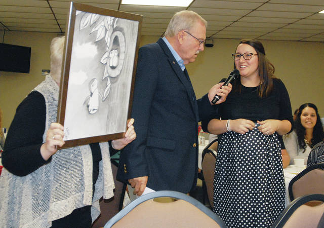 State Farm Agent Ashley Himes, far right, of Sidney, talks about her drawing of a bird learning to fly during the Gateway Arts Council's Bad Art Ball at the Palazzo, Thursday, Oct. 4. Interviewing her is Shelby County Sheriff John Lenhart. Holding Himes' art is Arlene Chilcote, of Sidney.