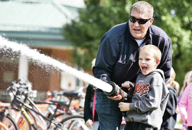 Austin Bohman, 7, son of Julie and Ryan Bohman, of Minster, gets pumped as he practices using a fire hose, with help from Minster firefighter Ryan Bergman, at Minster Elementary School, Friday, Oct. 12. Aiming a fire hose at a target was one of the activities Minster students did during the Minster Fire Prevention Program. Kindergarten students toured the Minster Fire Department. Elementary students practiced stop, drop and roll. Sixth-graders took part in a fire safety game show.
