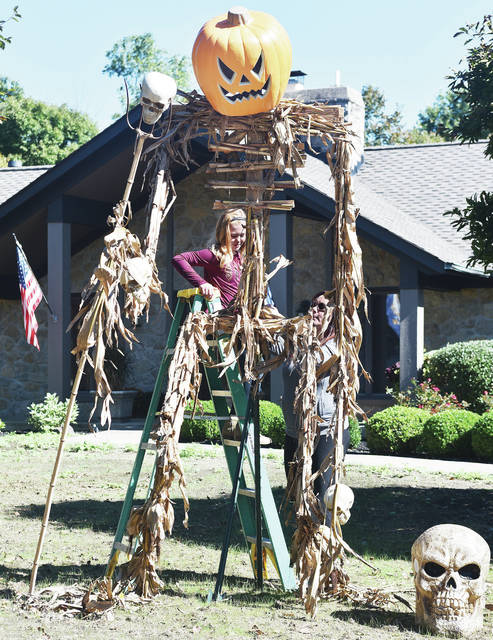 "Lindan Stewart, 9, daughter of Alan and Natalie Stewart, helps Diane Selanders, both of Sidney, add some corn stalks to a scarecrow in the front yard of Selanders' house Sunday, Oct. 14. Selanders and her husband Scott Selanders built the scarecrow. Selanders said she ""wanted something scary and haunting for Halloween."""