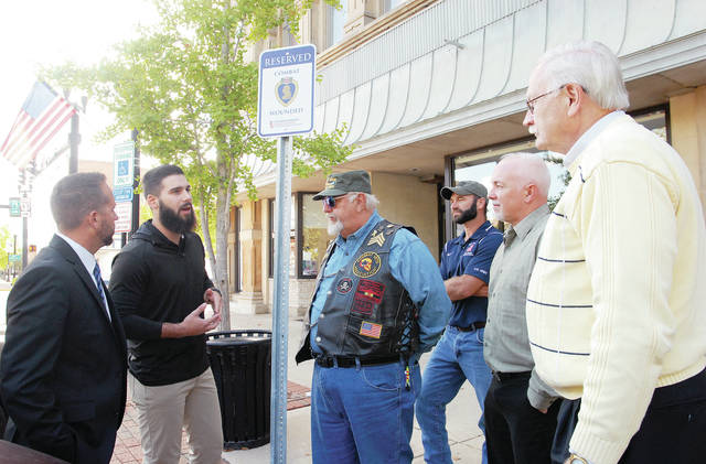Cole Hofmann, second from left, talks about the wounded combat veteran parking sign he helped to get installed in front of the Veteran's Services office recently. Listening to him are, left to right, Director of Veteran's Services Chris North, Vietnam veteran and Purple Heart recipient Richard Snider, President of Veteran's Services Commission Zack Bosslet, all of Sidney, Jamie Whitman, Sidney High School teacher, and Sidney Mayor Mike Barhorst.