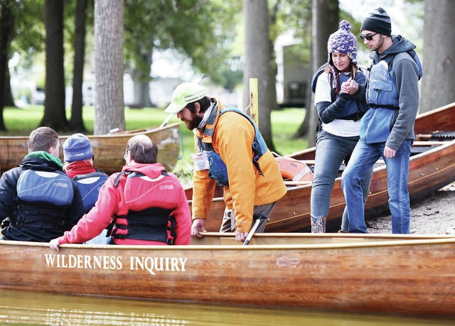 Jacob Balta, right to left, is helped into a canoe by Project Search Coordinator Patti Moore, both of Sidney, as Wilderness Inquiry trip leader Larry Raineri, of St. Paul, Minn., steadies the canoe, at Lake Loramie State Park, Friday, Oct. 19.