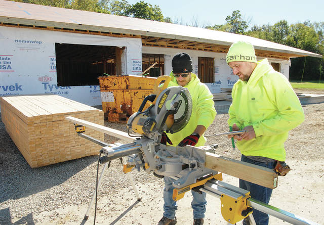 Westerheide Construction workers Nathan Hamaker, left, of DeGraff, and Justin Smith, of Sidney, cut wood for the Star House which is being built next to the Shelby County Sheriff's Office and will be used to house people working to break drug addictions.