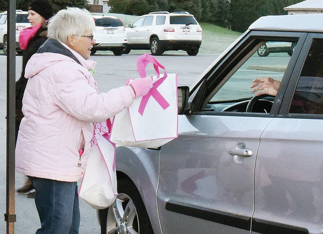 Barri Grandey, of Sidney, hands free breakfast to those who stop in to the Wilson Health event Brake for Breakfast Thursday, Oct. 18. The breakfast was held to raise awareness about breast cancer detection and mammograms.