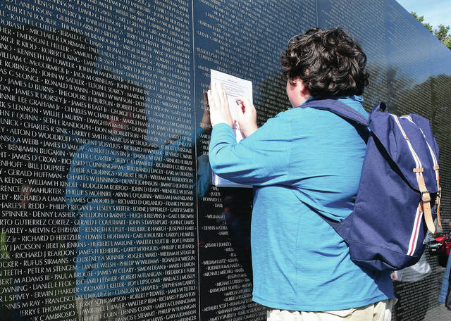Robbie Lynch uses a pencil and paper to get an etching off of the Vietnam Memorial Wall Friday, Oct. 19 during his Botkins 8th grade school trip to Washington D.C..