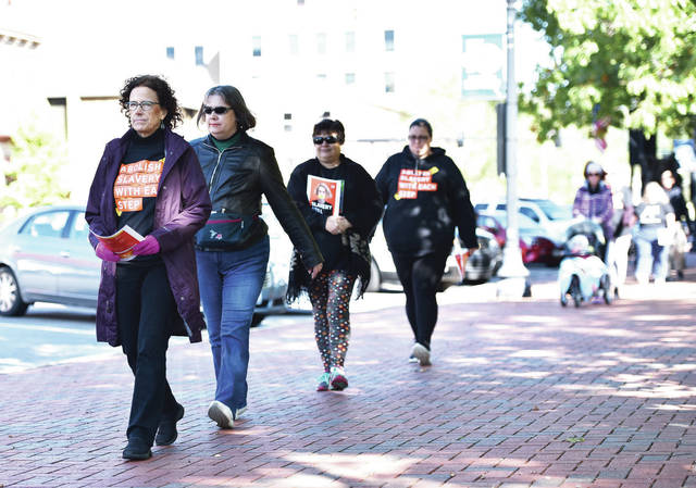 Pamela Wagner, left, of Sidney, leads a line of people in a walk around the courtsquare in downtown Sidney, Saturday, Oct. 20, to draw attention to human trafficking that is happening locally and internationally. Before the walk, a story was shared of a man from a local company who convinced a woman from Guatamala to marry him so she could move to the U.S. and then kept her in his house, monitoring her with a video security system, abusing her and making her sleep with his friends. People around the world also staged walks on the same day.