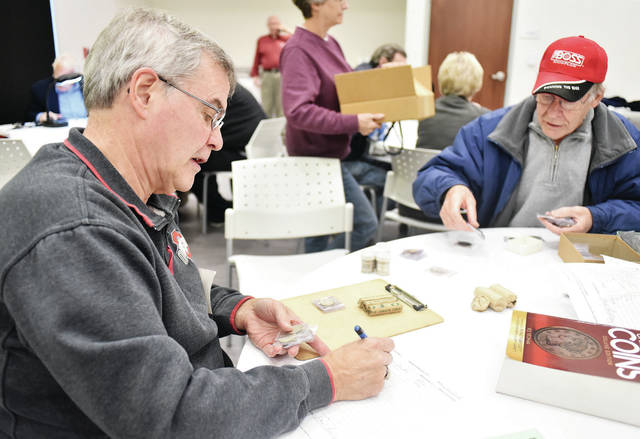 SC Collectibles owner Fred Billing, left, helps Steve Minton, both of Sidney, calculate the value of his coin collection during a free appraisal held by the Shelby County Coin Club at the Amos Memorial Library Tuesday, Oct. 23. People were lined out the door to sign up and have their coins appraised by local experts that volunteered their time. Information was also provided for proper coin care and how to sell a collection.