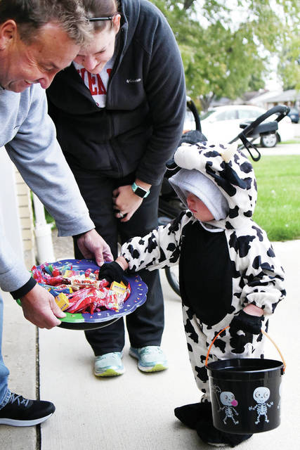 Aiden Wical, 1, escorted by his mom, Bethany Wical, gets some candy from Dan Schmiesing, all of Fort Loramie, during Fort Loramie Trick-or-Treating Thursday, Oct. 25.