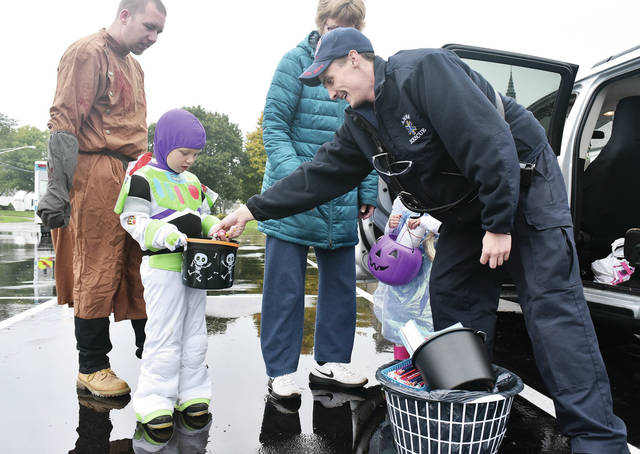 Josh Petty, far left, watches as his son Izik Petty, 5, both of Sidney, is given candy by Anna rescue worker Jesse Kean, of Quincy, during trick-or-treating in McCartyville Sunday, Oct. 28. With them are Barb Petty and Elizabeth Miller, 5, daughter of Matt and Michele Miller, all of Sidney. Trick or treat in Botkins has been rescheduled for Tuesday, Oct. 30, because of the rainy weather Sunday. It will be held from 5:30 to 7 p.m.