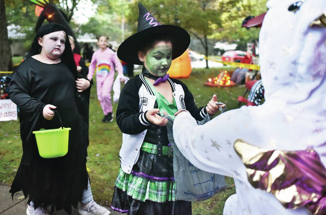 Chelsea Goble, far right, hands out candy to Kyra Jeter, 7, daughter of Erica and B.J. Jeter, as Tyleigh Henline, 8, all of Sidney, daughter of Christina and Tom Henline. Goble was handing out candy from her house on North Main Avenue Wednesday, Oct. 31. Goble had multiple animatronic monsters and ghouls in her front yard that had more than a few little kids wide eyed.