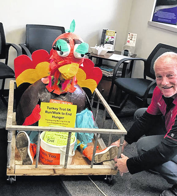 Tootie the Traveling Tutu'd Turkey visits with Tom Martin, owner of Sidney Body CarStar, as Martin repairs Tootie's crate recently at the auto body shop in Sidney. Sidney Body CarStar is one of the local businesses that sponsor the annual Turkey Trot 5K to Stomp Out Hunger in Shelby County. To register to participate in the Thanksgiving morning event, visit www.sidneyfirstpres.org.