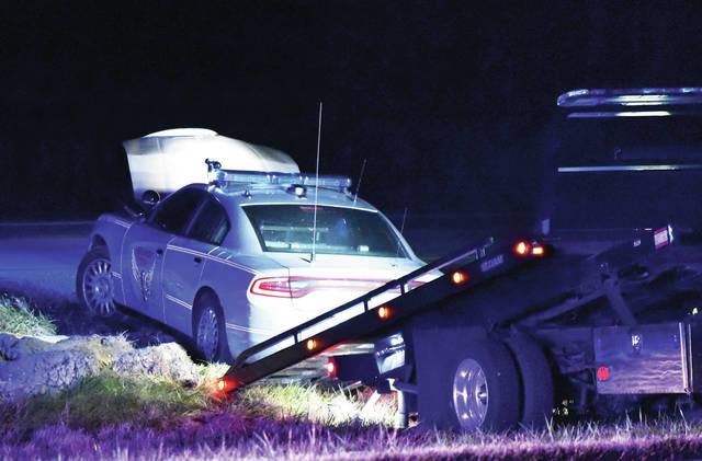 An Ohio State Highway Patrol car is loaded onto a tow vehicle after it was intentionally hit by a fleeing car, Thursday, Oct. 18, along Interstate 75 near mile marker 95.