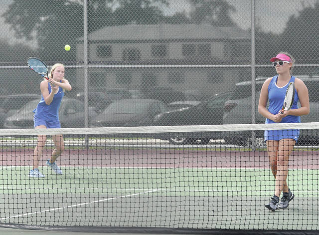 Lehman Catholic's Angela Brunner hits a backhand return as Sarah Gibson is in position at the net during the sectional tournament this week.   Rob Kiser | AIM Media Midwest