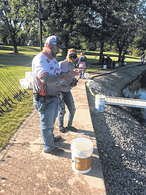 Nakiaya Arrone, right, daughter of Renee Arrone, of Sidney, gets help baiting her hook from one of the Shelby County Bassmasters.