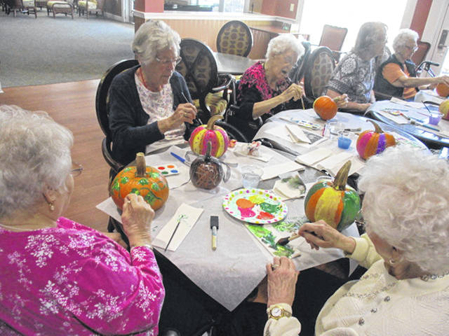 Residents of Elmwood Assisted Living in New Bremen paint pumpkins, recently, to celebrate the harvest season.