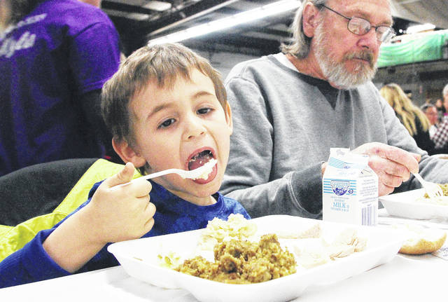 Eli Mash, left, son of Serena Cranford and Chris Schoffner, eats a spoonful of mashed potatoes next to his great grandpa, Orville Schoffner, both of Sidney at the 2017 Shelby County United Way Community Christmas Dinner.