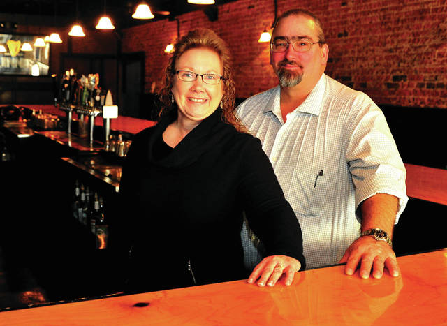 Nancy and Tom Elliott, of Shelby County, pose in the 311 Draft House, a tavern they purchased in Piqua.