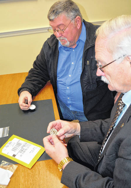 Shelby County Commissioner Bob Guillozet, right, and Sidney Mayor Mike Barhorst look at proofs of coins struck to commemorate the Shelby County's bicentennial, Monday, Nov. 26, in Sidney.