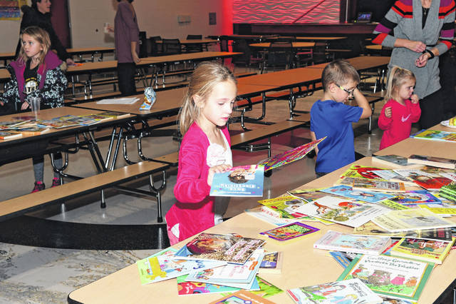 Marklin Rattermann, 6, daughter of Ashleigh and Andy Ratermann, of Botkins, selects books at Botkins School, Monday, Nov. 19, during the Fall Family Literacy Night.