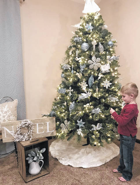 Jace Schlater, 4, son of Megan and Ryan Schlater, of Botkins, holds an ornament before placing it on the tree. The Schlater home is one of four stops on this year's Botkins Beautification Club's Christmas Tour of Homes.