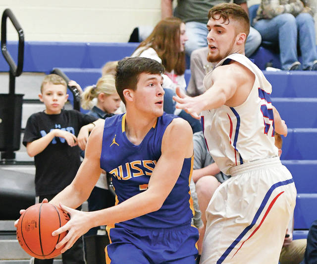 Russia's Jordan York looks to pass with pressure from Riverside's Lane Willoby during a nonconference game on Dec. 16, 2017. The Raiders will be trying for their sixth consecutive SCAL title this season.