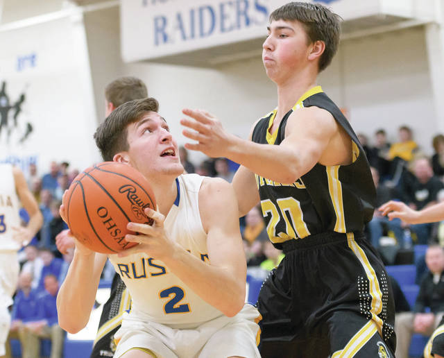 Russia junior forward Jordan York shoots with pressure from Botkins' Spencer Heuker during a Shelby County Athletic League game on Feb. 2 at Clair C. Naveau Gymnasium in Russia. Hueker averaged 10.3 points and 3.4 rebounds per game last season for Botkins.