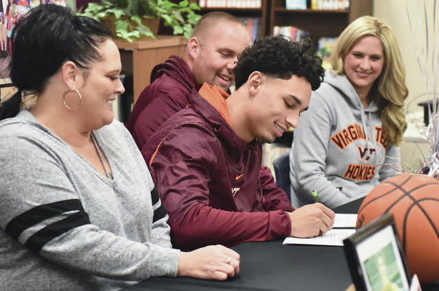 Andre Gordon, center, signs his national letter of intent to play at basketball for Virginia Tech on Monday at Sidney High School's library. Watching are, left to right, Tracy Williams, Johnny Perry and Nichole Perry.