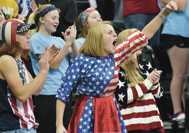 New Bremen volleyball fans cheer as their team begins to turn the tide on Monroeville at the Nutter Center in Dayton, Thursday, Nov. 8. New Bremen went on to beat Monroeville, 3-2, after falling behind 0-2. Fans dressed in patriotic red, white and blue.