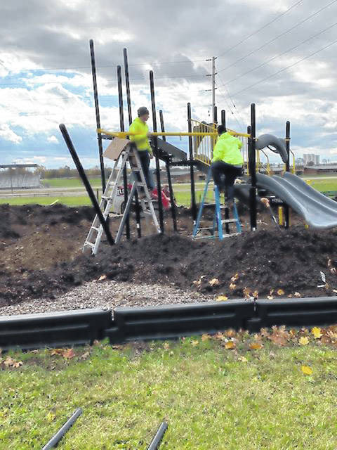 Spectra Contract Flooring employees Kenny Byler and Martin Byler install playground equipment at Emerson Elementary School Tuesday morning. Old playground equipment was removed from the site for the installation of the new equipment. The project is being funded by the school's PTO.
