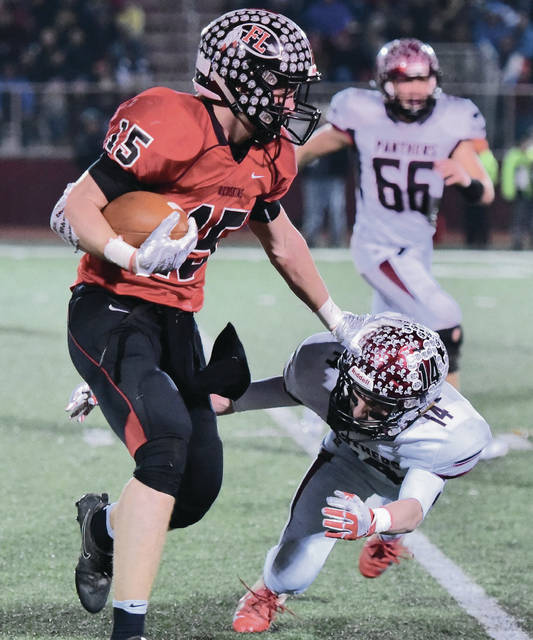 Fort Loramie's Mark Seger tries to avoid McComb's Aaron Davis during a Division VII state semifinal on Saturday at Wapakoneta's Harmon Field.