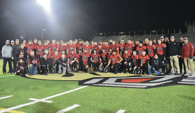 Fort Loramie players and coaches pose for a team photo after beating Convoy Crestview 48-20 in a Division VII regional final on Saturday at Lima Spartan Stadium.