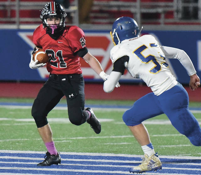 Fort Loramie's Carter Mescher runs as Lehman Catholic's Mitchell Sollmann closes in during a Division VII regional semifinal last Saturday in Piqua. Mescher has run for 539 yards and seven touchdowns and has caught 33 passes for 529 yards and six touchdowns.