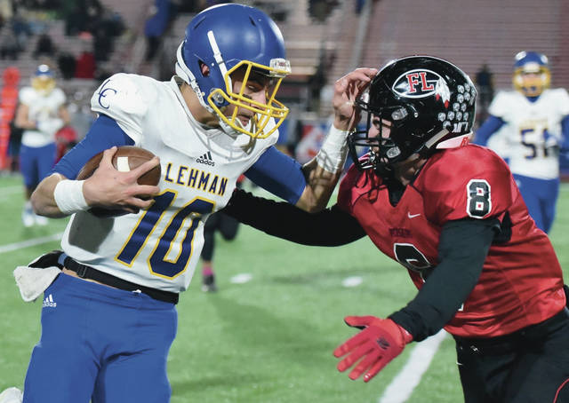 Lehman Catholic's Elliott Gilardi tries to avoid a tackle by Fort Loramie's Carson Moore during a Division VII regional semifinal on Saturday in Piqua.